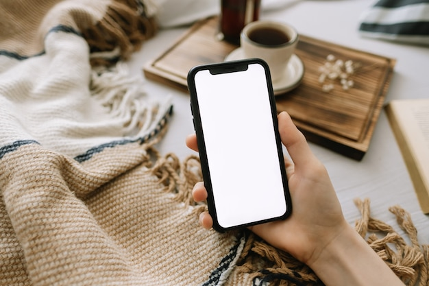 흰색 화면이있는 스마트 폰을 들고 집에서 침대에 앉아 커피를 마시는 여자.