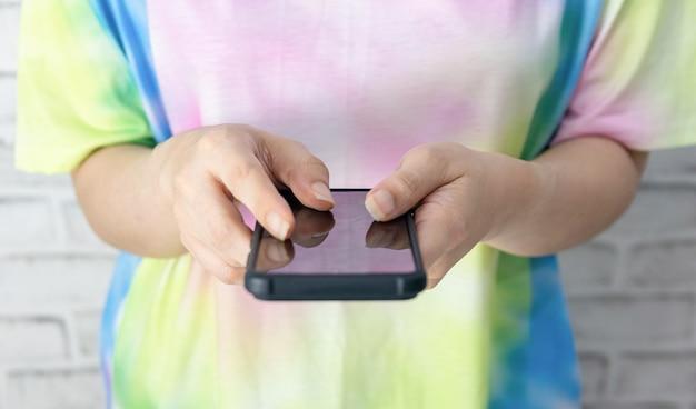 통신 기술이 탑재된 스마트폰을 들고 있는 여성