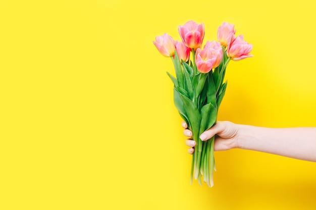 黄色の手にピンクのチューリップの春の花束を持っている女性