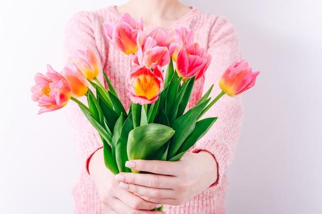 ピンクのチューリップの春の花束を手に持っている女性。