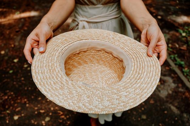 밀짚 모자를 들고 가을 배경에 자선을 구걸하는 여자. 거리 공연을 위한 빈곤, 구걸 또는 팁 개념