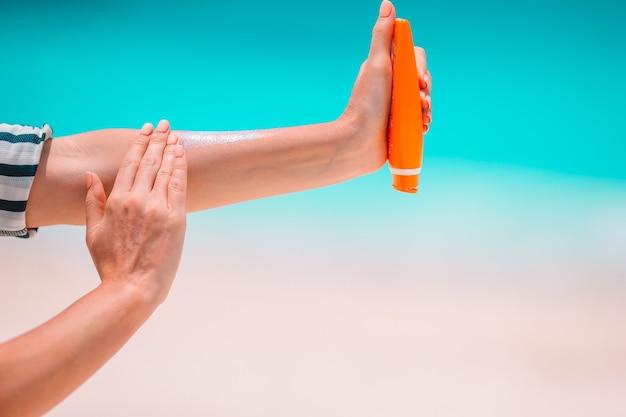 선크림을 들고 열대 해변에서 선크림으로 손을 문지르는 여성