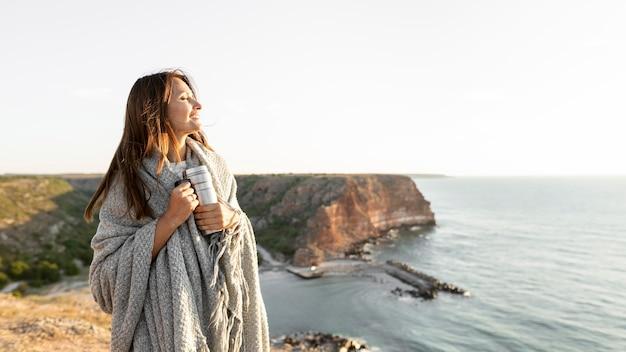 コピースペースのある海岸を歩きながら魔法瓶を持っている女性