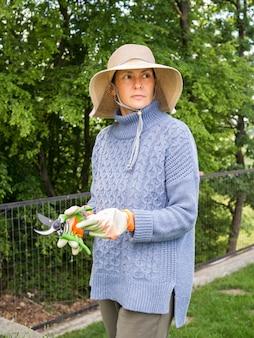 葉を切るためのツールを保持している女性