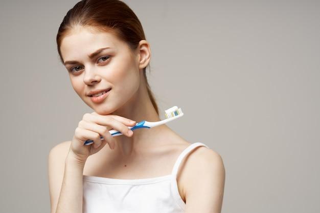 Женщина держит зубную щетку с пастой в руках крупным планом гигиены полости рта