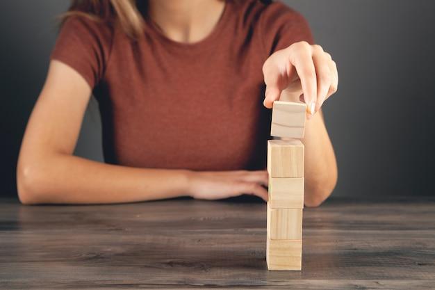 나무 큐브의 탑을 들고 여자