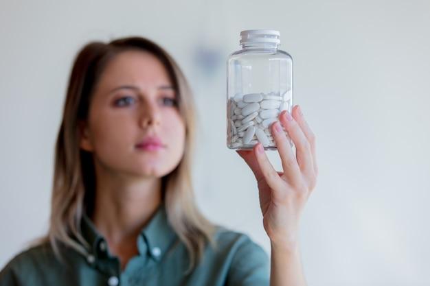 白い錠剤で透明な瓶を保持している女性。