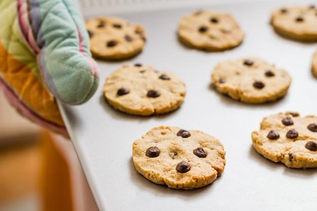 Женщина держит поднос с домашним печеньем в ярких кухонных перчатках