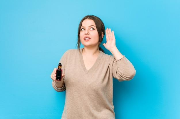 ゴシップを聴こうとしている気化器を持っている女性