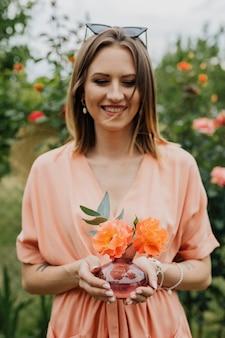 オレンジ色のバラの花瓶を持っている女性
