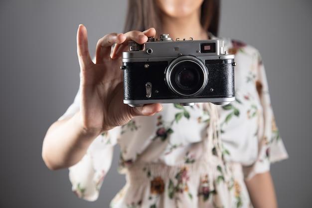 Женщина держит старинный фотоаппарат