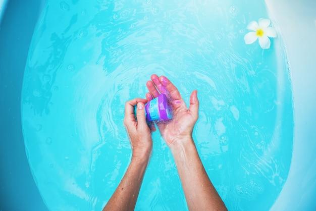 Женщина держит фиолетовую бомбу в ванной