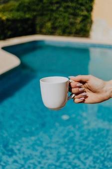 プールサイドで白いコーヒーカップを保持している女性