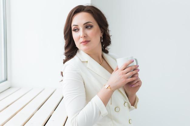 白い一杯のコーヒーを持っている女性