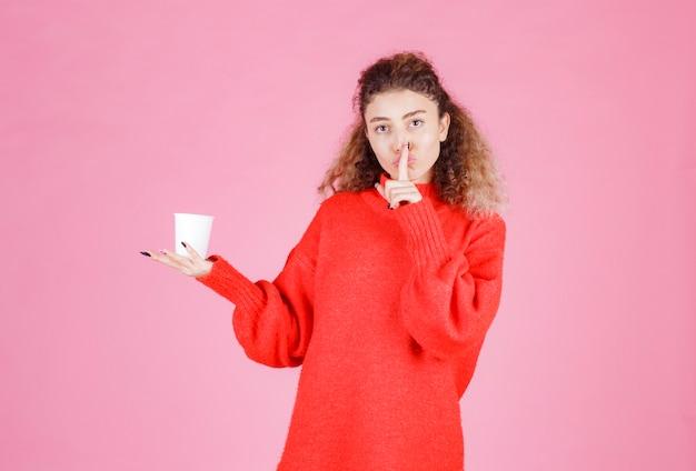 白い使い捨てカップを持って沈黙を求める女性。