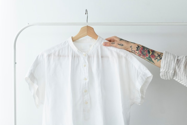스튜디오에서 흰 셔츠를 들고 있는 여자