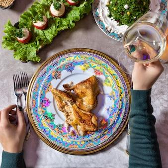 白ワイン、テーブルトップビューで鶏肉の食事を保持している女性