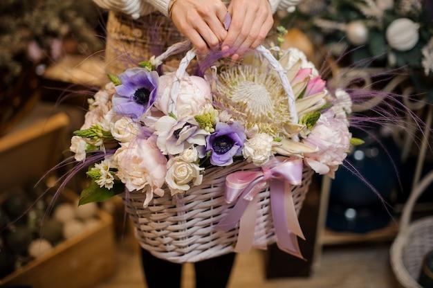 부드러운 흰색, 분홍색, 보라색 꽃 바구니를 들고 여자