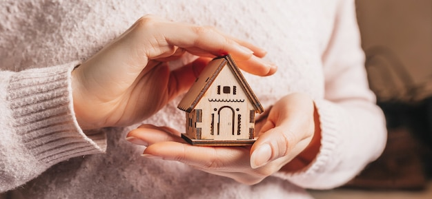 Женщина, держащая деревянный дом руками с солнцем на светло-розовом фоне. милый дом