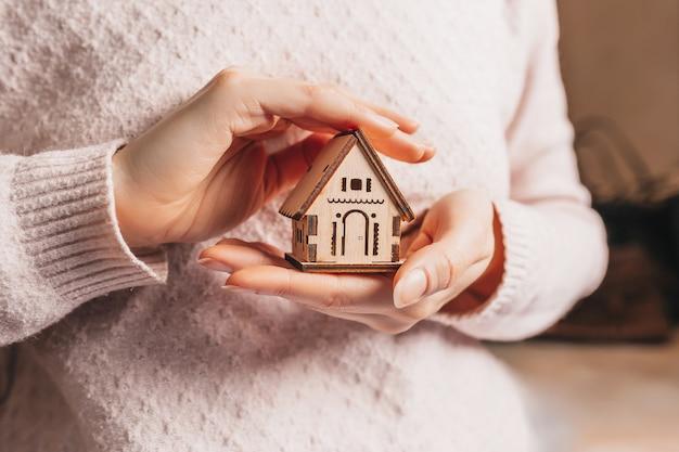 薄ピンク色の表面に太陽と彼女の手で木造住宅を保持している女性。甘い家