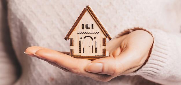 手で木造家屋を持っている女性