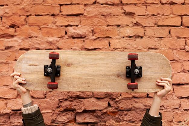 木製のスケートボードを持っている女性