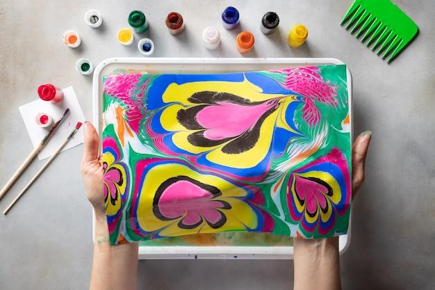 絵の具やツールでテーブルの上に、抽象的な描画を保持している女性