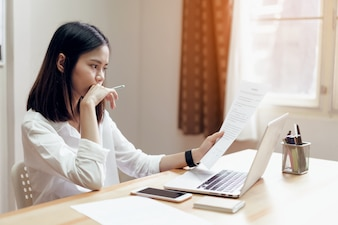 Woman holding agreement documents and using laptop on table in office room, to plan.