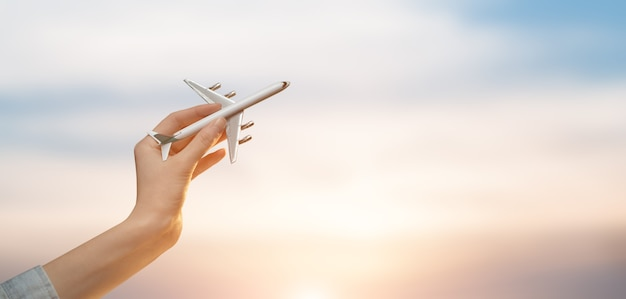Woman holding airplane in hands and flying over the sunset background