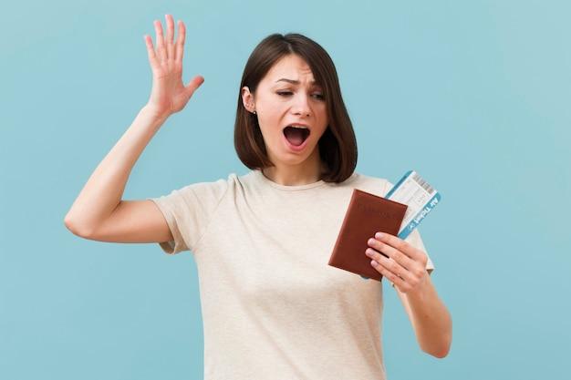 Женщина, держащая билеты на самолет и паспорт
