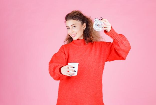 Donna che tiene una sveglia e una tazza di caffè che indica la sua routine mattutina.