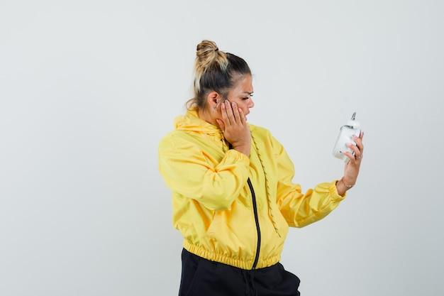 Женщина держит будильник в спортивном костюме и смотрит с тревогой. передний план.