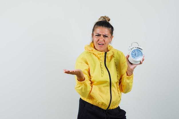 Женщина держит будильник в спортивном костюме и выглядит смущенным, вид спереди.