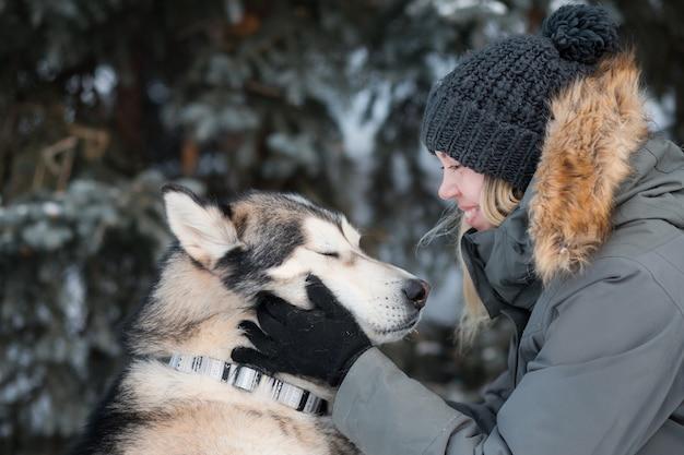 冬の喜びから目を閉じてアラスカンマラミュートの顔を保持している女性