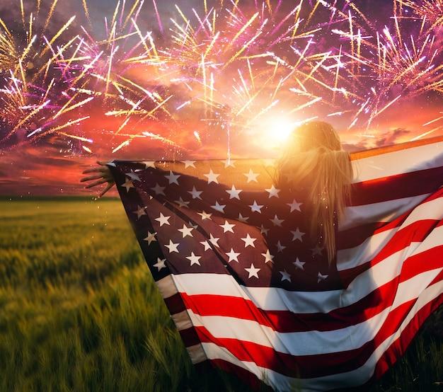 Женщина, держащая американский флаг на закате с фейерверком, америка празднует 4 июля