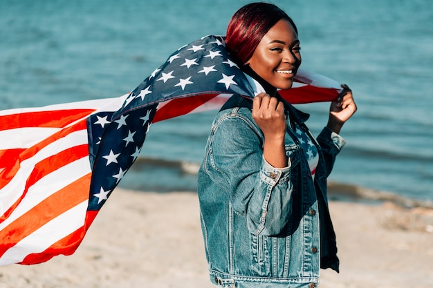 Woman holding american flag behind back fluttering in wind