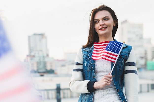 Woman holding american flag near chest