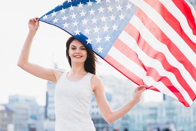 Женщина держит американский флан и машет им