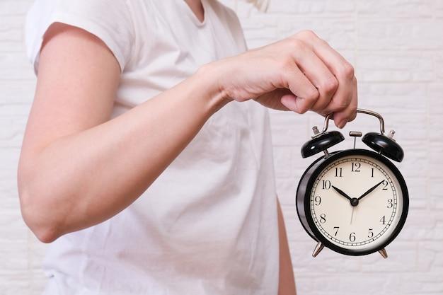 10時を示す目覚まし時計を保持している女性は、人々は時間、期限の概念を評価し、評価する必要があります。