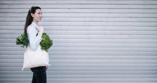 에코 가방을 들고 여자는 식료품으로 가득합니다. 야채와 과일이 가방에 걸려 있습니다. 생태 또는 환경 보호 개념. 모의를위한 흰색 에코 백.