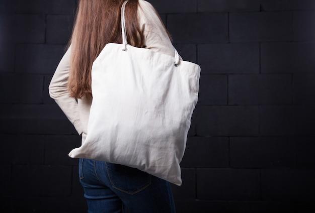 로고에 대 한 빈 가방을 들고 여자