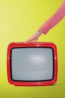 Женщина, держащая старый красный телевизор