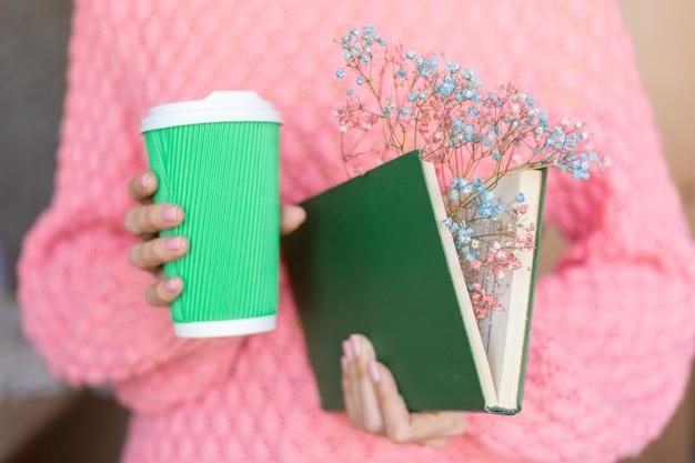 내부 말린 꽃의 꽃다발과 커피 종이 컵과 함께 펼친 책을 들고 여자