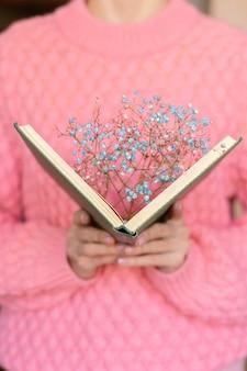 내부 말린 꽃의 꽃다발과 함께 열려있는 책을 들고 여자