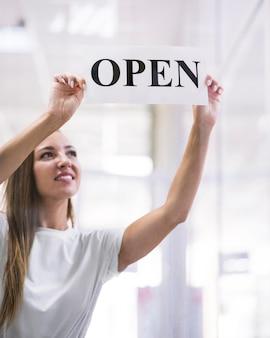 Женщина, держащая открытый знак