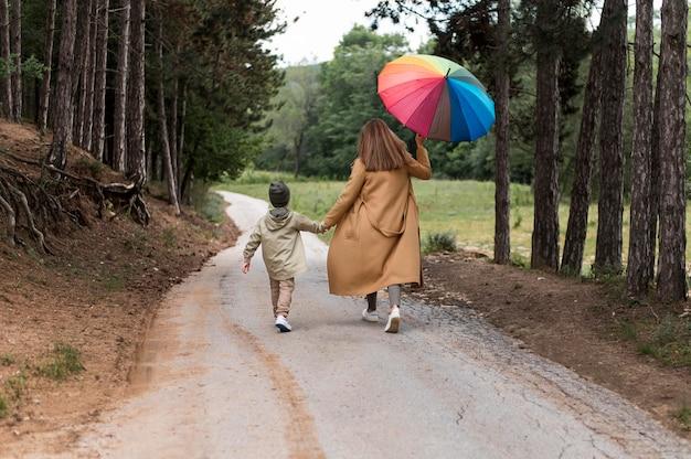 手で傘と息子を保持している女性