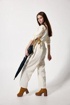彼女の手で傘を持っている女性ファッション白いスーツスタジオモダンなスタイル