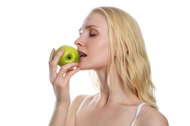 白い背景の上の新鮮な青リンゴを保持し、食べる女性。ダイエットコンセプト。健康的なライフスタイル