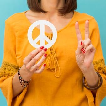 Женщина держит и делает знак мира