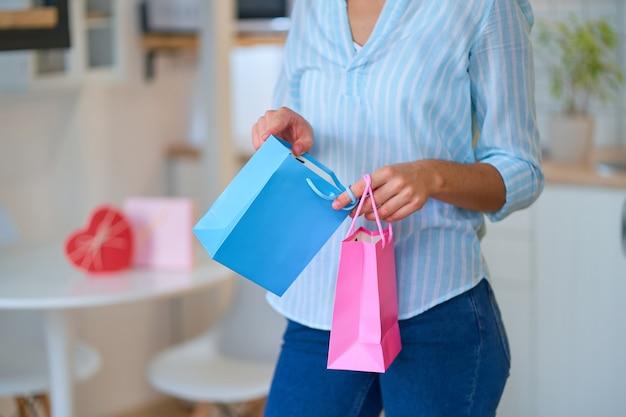 Женщина держит и открывает цветные подарочные пакеты